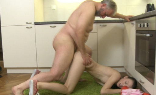 Katia kneels besides her older lover and he shoots cum all over her face and tits.